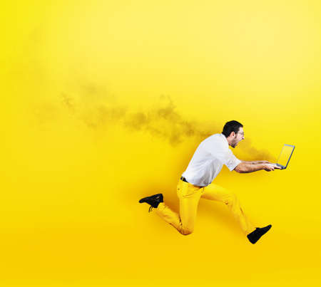 Businessman runs with laptop on fire in hand. Yellow style