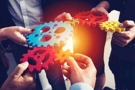 Business team connect pieces of gears. Teamwork, partnership and integration concept Stock fotó