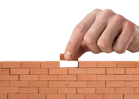 Businessman puts a brick to build a wall. Concept of new business, partnership, integration and startup Stockfoto