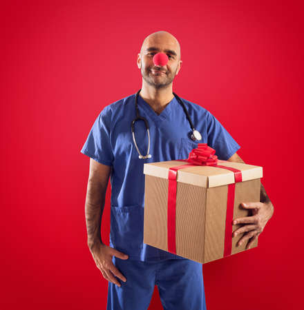 Nurse with clown nose and gift on red background Stock Photo