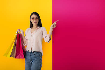 Happy woman with shopping bags in hand indicates something