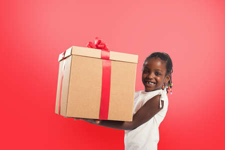 Happy little girl with a Christmas gift. Stock Photo