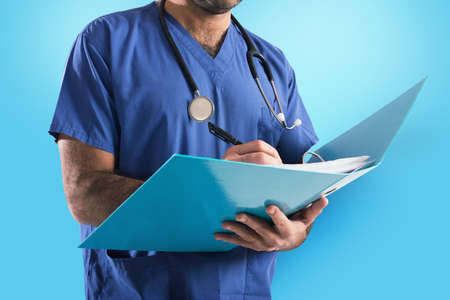 Doctor with stethoscope writes on medical record Imagens