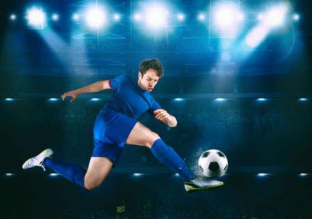 Napastnik uderza piłkę akrobatycznym kopnięciem w powietrze na stadionie