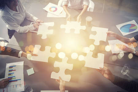 Business people join puzzle pieces in office.