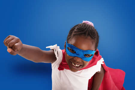 Child acts like a superhero to save the world on blue Imagens