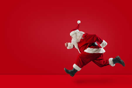 Santa Claus runs fast on red Stock Photo