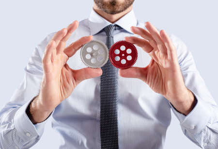 Businessman connects gears. Teamwork and partnership concept