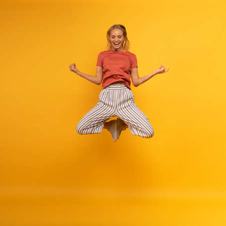 Blonde girl jumps in yogas position. Relax concept. Yellow background
