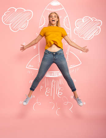La fille saute sur fond rose prête à voler comme une fusée. Concept de liberté, d'énergie et de vitalité