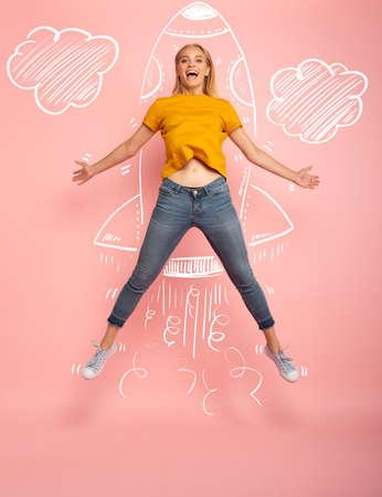 Mädchen springt auf rosa Hintergrund, der bereit ist, wie eine Rakete zu fliegen. Konzept von Freiheit, Energie und Vitalität