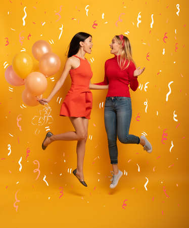 Girls ready for a party with balloons. Joyful an happiness expression. Yellow background Stockfoto - 131309893