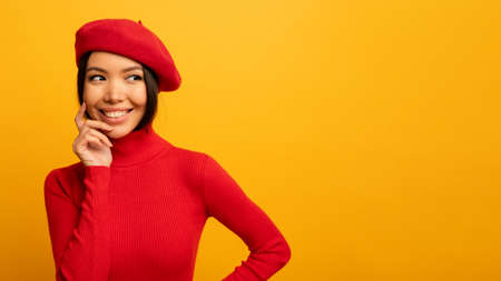 Brunette girl smiles with red hat and cardigan. Emotional and joyful expression. Yellow background Stockfoto - 131309896