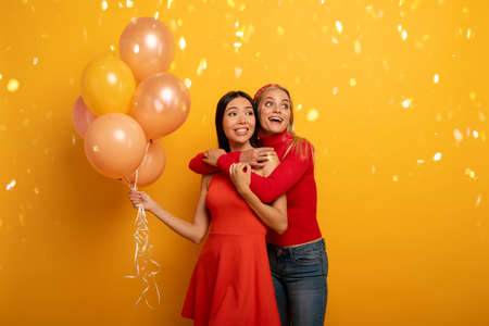 Girls ready for a party with balloons. Joyful an happiness expression. Yellow background