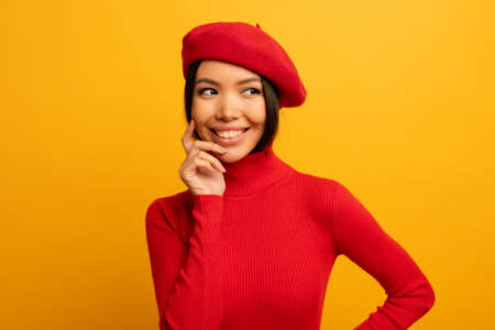Brunette girl smiles with red hat and cardigan. Emotional and joyful expression. Yellow background Stockfoto - 131309972