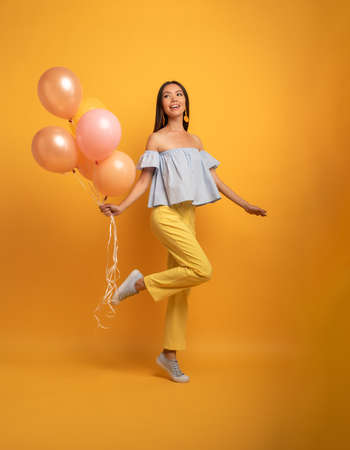 Girl ready for a party with balloon. Joyful an happiness expression. Yellow background Stockfoto
