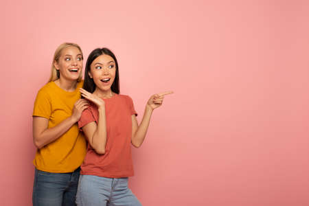 Two girls indicates something. Amazed expression face. Pink background with blank space for your text Stockfoto - 131309980
