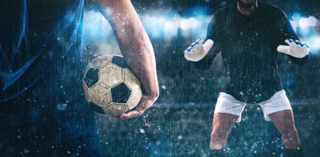 Soccer scene at night match with close up of a soccer striker holding the ball against the opposing goalkeeper
