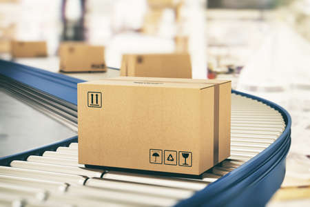 Boîtes en carton sur rouleaux convoyeurs prêtes à être expédiées par coursier pour distribution