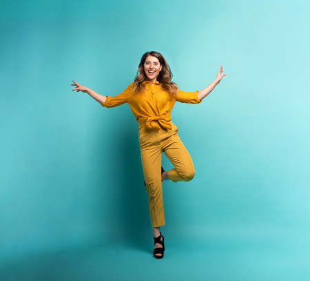 Brunette girl with a yellow clothes jumps over a cyan Stockfoto