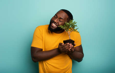 Happy boy loves a small tree ready to be planted. Concept of forestation