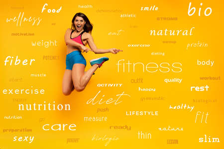 Sport woman jumps on a yellow with most important fitness terms. Happy and joyful expression. Stockfoto