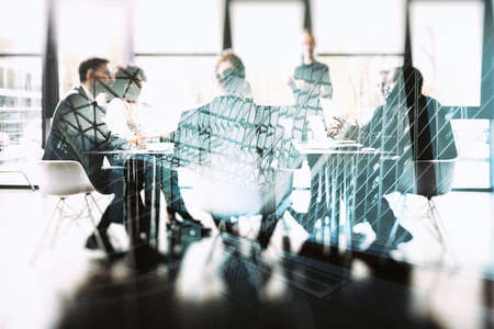 Background concept with business people sitting at the meeting table in the office near a window glass. Double exposure effects