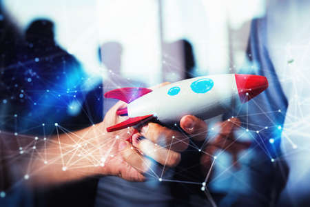 Businessman launches his startup company. Hand holding a toy rocket. double exposure with network effects