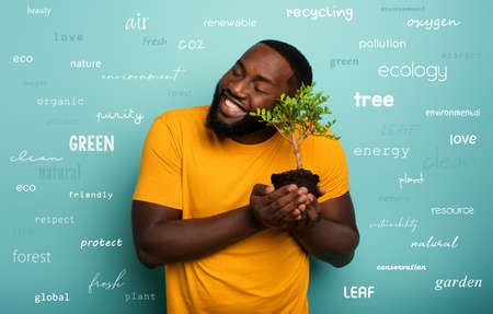 Happy boy hugs a small tree ready to be planted over a light blue color. Concept of forestation, ecology and conservation with most important terms