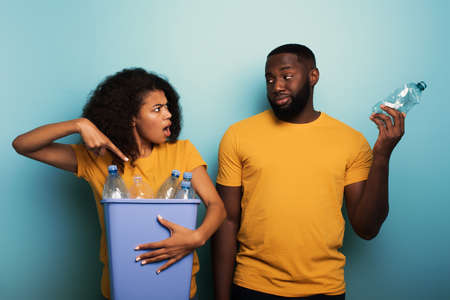 Happy couple hold a plastic container with bottles over a light blue color. Concept of ecology, conservation, recycling and sustainability Stok Fotoğraf