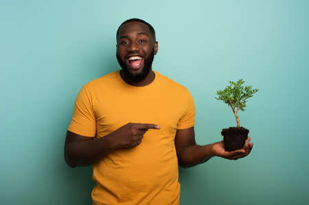 Happy boy indicates a small tree ready to be planted over a light blue color. Concept of forestation, ecology and conservation Stockfoto