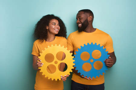 Couple with gears in hand over light blue background. Concept of integration, union and partnership Stockfoto - 132347887