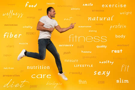 Sport man jumps on a yellow background. Happy and joyful expression. With most important fitness and diet terms