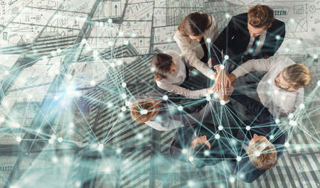 Handshaking business person in office. concept of teamwork and partnership. double exposure with network effects.