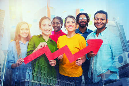 Young happy and colorful business team hold a red statistical arrow. Concept of growing, succesful and profit