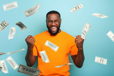 Boy wins money. Amazed and surprised expression face. Light blue background