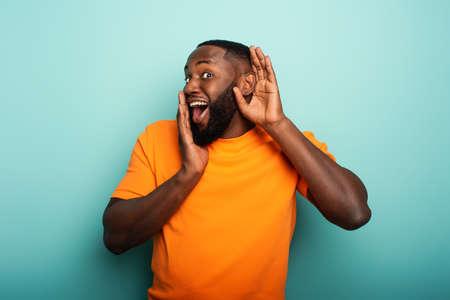 Mann hört eine geheime Nachricht. Konzept der Neugier und Klatsch. Erstaunter Ausdruck