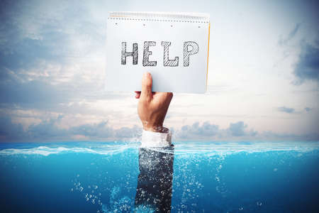Empresario ahogándose en el mar con una mano sosteniendo una hoja de papel con ayuda escrita Foto de archivo