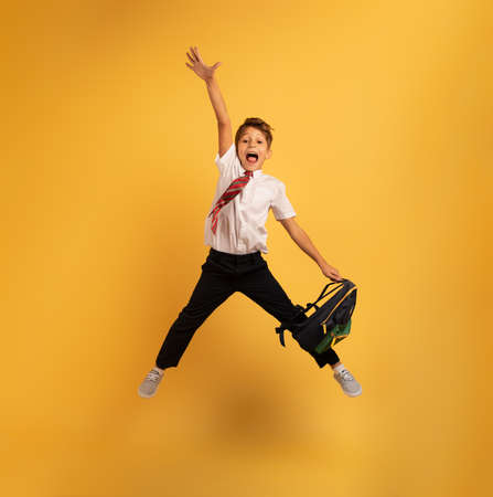 Young boy student jumps high happy for the promotion. Yellow background
