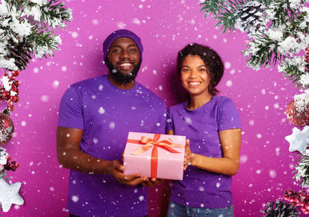 Happy and joyful couple show their Christmas present. Violet background Stock fotó