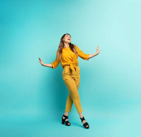 Brunette girl with a yellow clothes walks over a cyan background. Concept of fashion and shopping with joyful expression