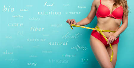Girl measures with the meter the diet results. Happy and joyful expression. Cyan background with diet terms 스톡 콘텐츠