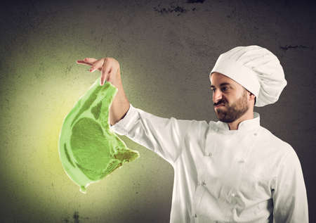 Chef with radioactive and contaminated meat steak. Concept of pollution, unhealthy and harmfulness