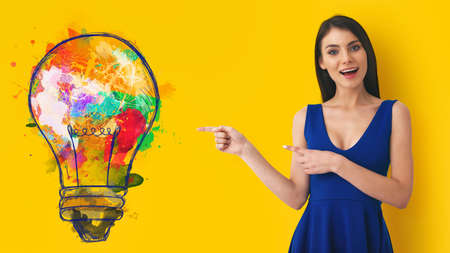 Young woman pointing at big stylized light bulb on yellow background. Concept of idea and creativity 스톡 콘텐츠