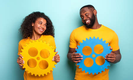 Couple with gears over light blue background. Concept of integration, union and partnership 스톡 콘텐츠