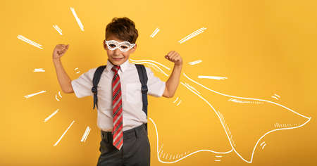 Young boy student acts like a super hero. Imagens