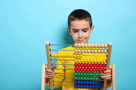 Child tries to solve mathematical problem with abacus. Cyan background