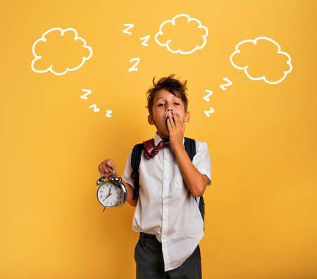 Young child student with ringing alarm clock is lazy going to school. Yellow background. Stock Photo
