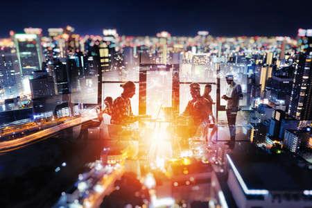 Silueta de jóvenes empresarios trabajan juntos en la oficina por la noche en un horizonte