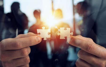 L'homme d'affaires se joint à deux pièces de puzzle. Concept de travail d'équipe et de partenariat. double exposition avec effets de lumière